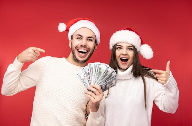 Фотография сладкой парочки в рождественских шапках, счастливых праздников, держит деньги в долларах. мужчина и женщина влюблены, выглядят счастливыми и улыбаются, изолированные на красном фоне.