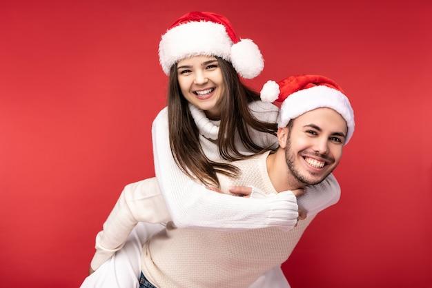 Фотография сладкой парочки в новогодних шапочках, радуясь праздникам, она прыгнула ему на спину. мужчина и женщина влюблены, выглядят счастливыми и улыбаются, изолированные на красном фоне.