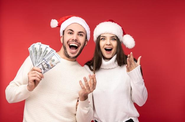 Фотография сладкой парочки в рождественских шапках, держит деньги в долларах, продажи. мужчина и женщина влюблены, выглядят счастливыми и улыбаются, изолированные на красном фоне.