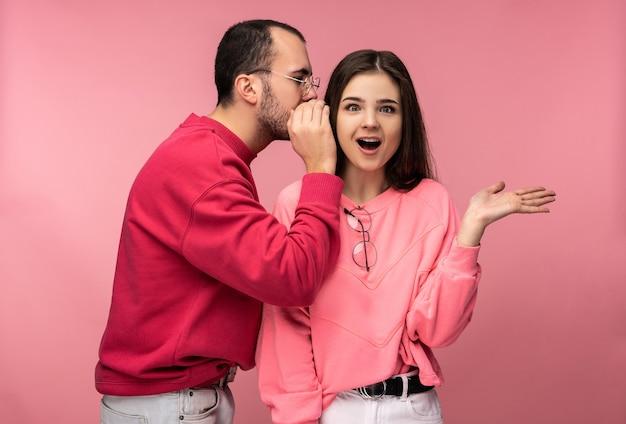 달콤한 커플의 사진, 남자는 그의 여자 친구에게 몇 가지 비밀이나 판매를 속삭이고 그녀는 놀랐습니다, 분홍색 배경 위에 격리.
