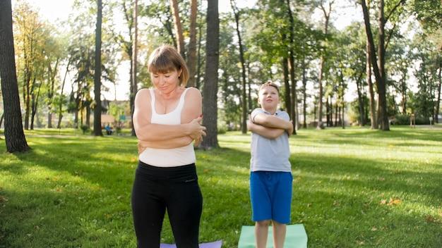 잔디 공원에서 어머니와 함께 요가를 하는 10대 소년의 사진. 숲에서 함께 피트니스 및 스트레칭 운동을 하는 가족