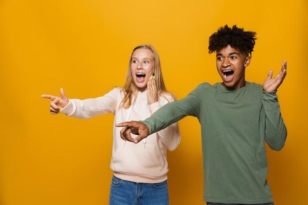黄色の背景の上に分離された、コピースペースで笑って指を脇に向けて笑っている歯列矯正器を持つ10代の友人の男性と女性の写真