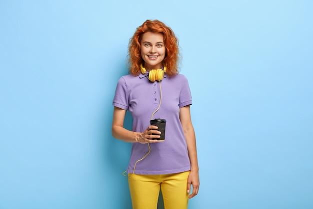 십대 소녀의 사진은 뜨거운 커피를 좋아하고, 종이컵을 들고, 헤드폰을 통해 오디오 트랙을 청취합니다.