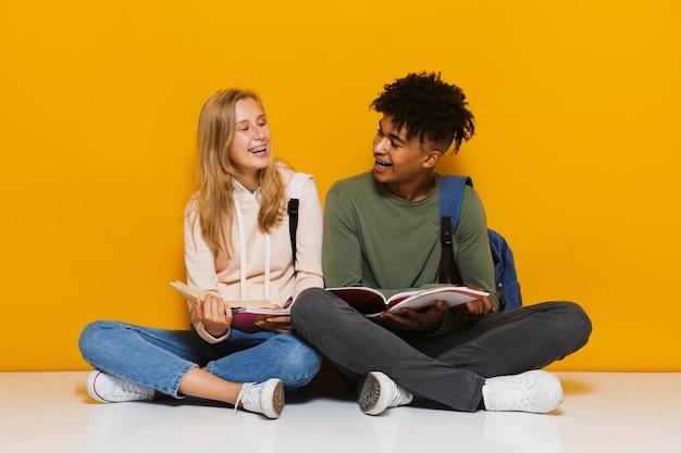黄色の背景の上に分離された、足を組んで床に座って本を読んで使用している10代の学生の写真