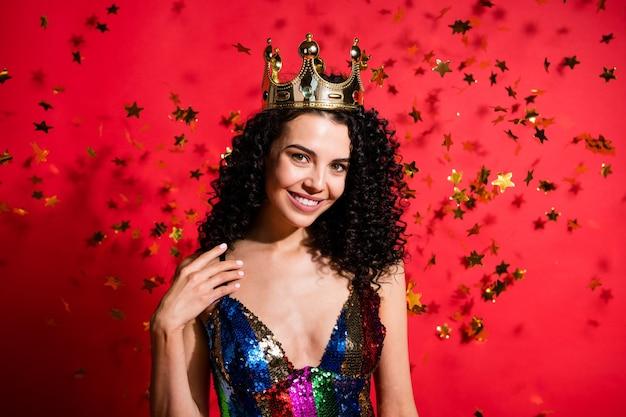 부드러운 소녀 별의 사진은 빛나는 미소 손바닥 가슴을 입고 황금 왕관 광택 빛나는 드레스를 입고 생생한 붉은 색 배경에 고립