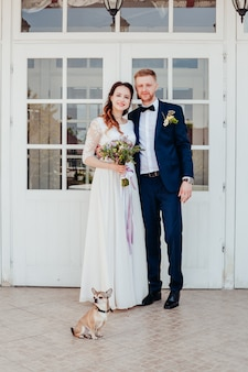 Фото жениха и невесты в день свадьбы с маленькой собачкой