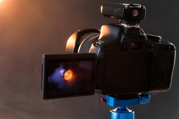 Фотография камеры на голубом штативе, который фотографирует в студии профессиональное осветительное устройство в дыму. студийное освещение и дымовое оборудование. рекламная фотосессия осветительного устройства