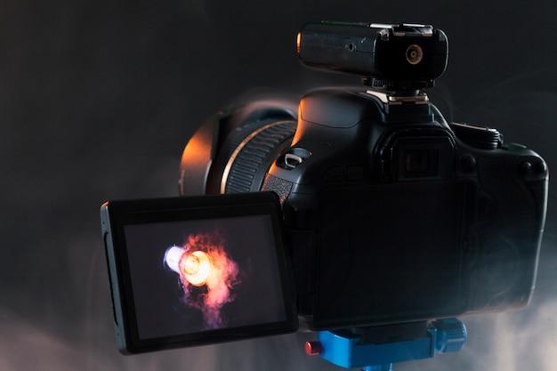 スタジオで煙の中のプロの照明器具を撮影する青い三脚上のカメラの写真。スタジオライトと煙機器。照明器具の広告撮影会