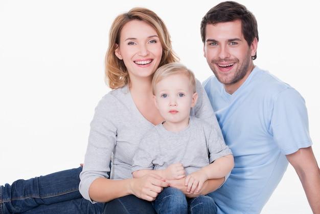 小さな子供が座っている幸せな若い家族の写真