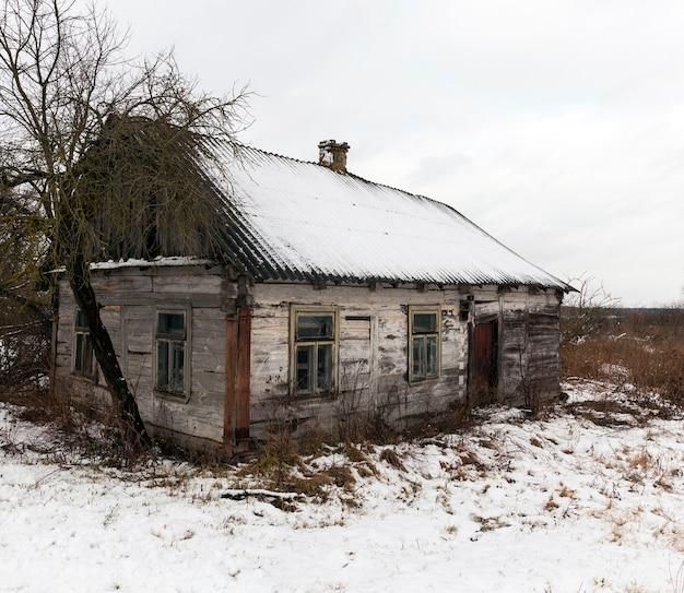 降雪後に雪に覆われた古い倒壊した一軒家の写真