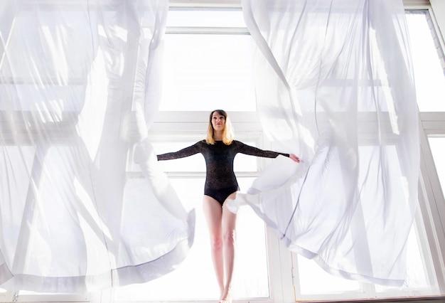 Фотография молодой женщины стоит на окне среди открытых занавесок.