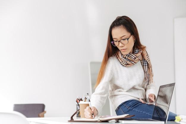 携帯電話を使用して眼鏡をかけ、オフィスのテーブルに座って彼女の日記に書いているアジアの女性労働者を考える写真