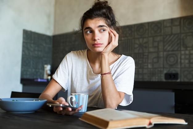 Фотография думающей женщины брюнетки, читающей книгу и использующей мобильный телефон во время завтрака на кухне дома