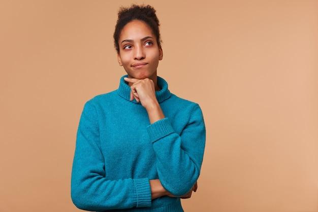 青いセーターを着ている巻き毛の黒い髪の若いアフリカ系アメリカ人男性を考える写真。あごに触れ、コピースペースでベージュの背景の上に孤立して見上げます。