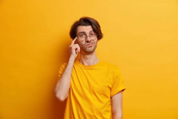 Фотография задумчивого молодого европейца, держащего палец на виске, представляет, что кто-то носит круглые очки, а повседневная футболка, изолированная на желтой стене, делает важный вариант выбора.