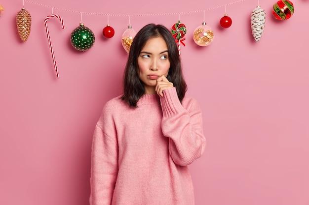 사려 깊은 갈색 머리 아시아 여자의 사진은 새해 포즈 전에 집 장식에 대해 생각하는 얼굴에 손을 유지 캐주얼 점퍼를 입은 불쾌한 스탠드