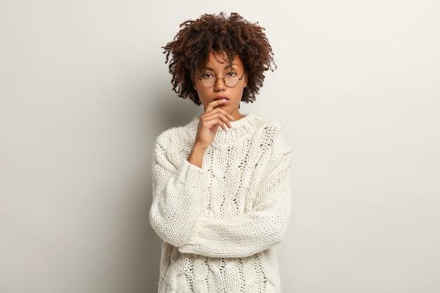 На фото задумчивая темнокожая женщина, вьющиеся волосы, серьезный вид, задумчивая, прямолинейно, в свитере с длинным рукавом, изолирована на белой стене. концепция мышления