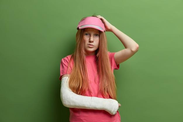思いやりのある優柔不断な女性の写真は頭を掻き、彼女に起こった事故についてのすべての詳細を思い出そうとします、石膏で腕を骨折し、カジュアルな服を着て、緑の壁に隔離されました