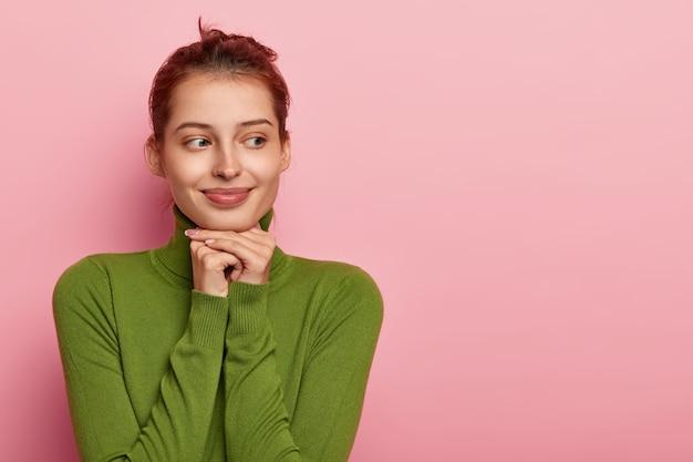 사려 깊은 유쾌한 유럽 소녀의 사진은 턱 아래에 양손을 유지하고 멀리 보이며 녹색 캐주얼 점퍼를 입고 분홍색 벽에 고립 된 여유 공간을 제쳐두고