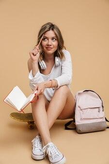ヘッドフォンで日記を書き、ベージュの壁に隔離されたスケートボードに座っている思いやりのある10代の少女の写真