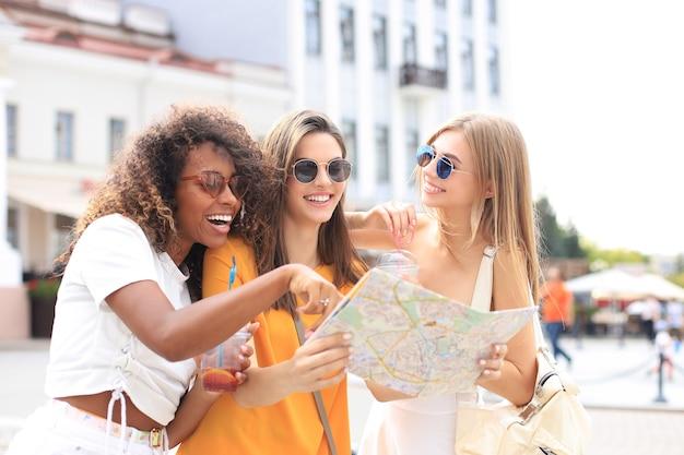 屋外観光を楽しんでいる3人の女の子の写真。地図で街を探索する美しい女性観光客。