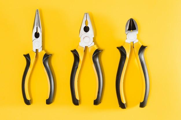 Фото трех желтых и черных плоскогубцев, изолированных на желтом фоне