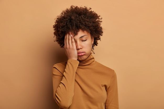 На фото уставшая кудрявая женщина закрывает лицо ладонью, чувствует переутомление и усталость, хочет спать, наклоняет голову, носит повседневную водолазку.