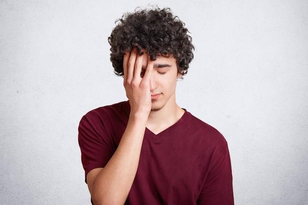 Фотография уставшего перегруженного красавца с вьющимися темными волосами, закрывающего лицо рукой, выглядит расстроенной. подросток держит глаза закрытыми