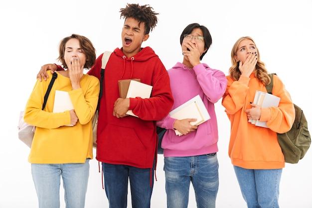 あくびをして孤立して立っている友人の学生の疲れた若いグループの写真。