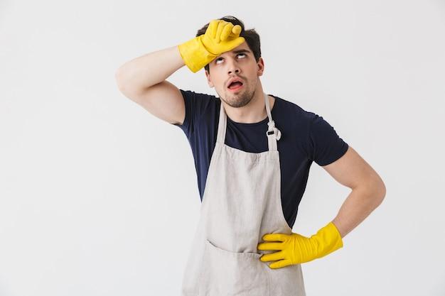 Фото усталого молодого человека в желтых резиновых перчатках для защиты рук, вытирающего пот во время уборки дома, изолированного на белом