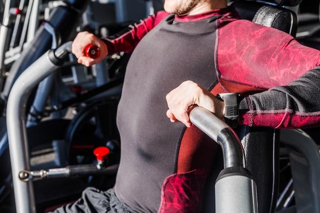 Фотография тренажерного зала тренажерного зала для человека, накачивающего мышцы, сидя на скамейке. грудь упражнение с отягощением. он берет руки перед грудью в фитнес-центре.