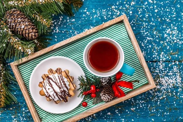 スプルース、雪、新年の装飾が施されたテーブルにお茶とケーキのマグカップが付いているトレイの写真