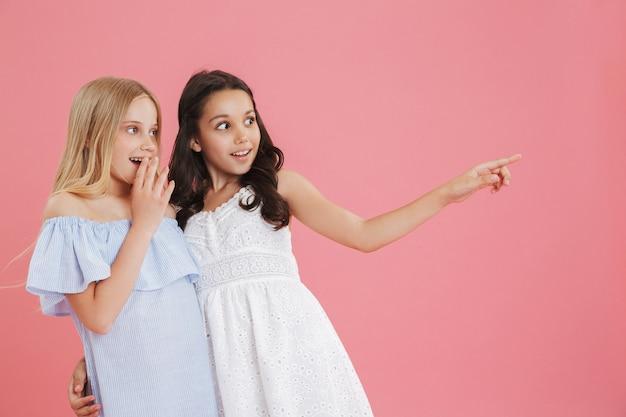 Фотография двух забавных детей 8-10 лет в платьях, смотрящих в сторону и указывающих пальцем на copyspace.