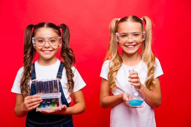 두 명의 아름다운 작은 숙녀 스마트 학교 아이들의 사진은 교사에게 튜브에 결과를 보여주는 화학 실험을 안전 사양 전체 티셔츠 격리 된 붉은 색 배경을 착용합니다