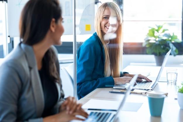 두 명의 비즈니스 여성이 코워킹 스페이스의 분할된 책상에서 노트북으로 작업하면서 서로를 바라보는 사진입니다. 사회적 거리의 개념입니다.