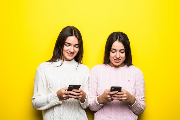 노란색 벽에 고립 된 채팅 두 명랑 소녀의 사진.
