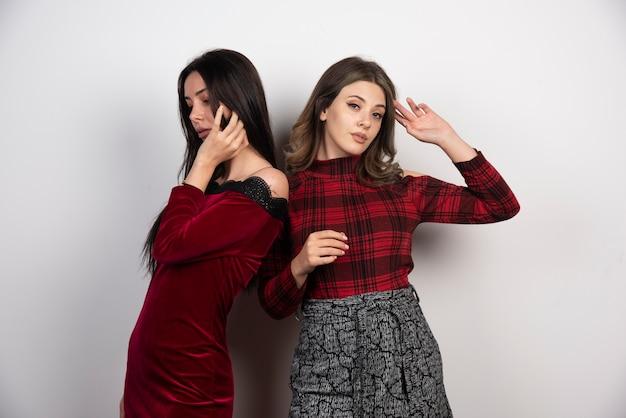 서서 흰 벽에 포즈를 취하는 두 여자 친구의 사진.