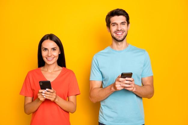 2人の面白い男女性のカップルの写真ソーシャルネットワークを読んで電話の腕を持っているコメントを投稿するカジュアルな青オレンジ色のtシャツを着る孤立した黄色の壁