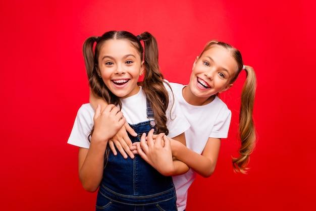 Фотография двух забавных симпатичных маленьких дам, проводящих выходные вместе, приятели наслаждаются лучшими праздниками, носят джинсы в целом белая футболка, изолированный красный цвет фона