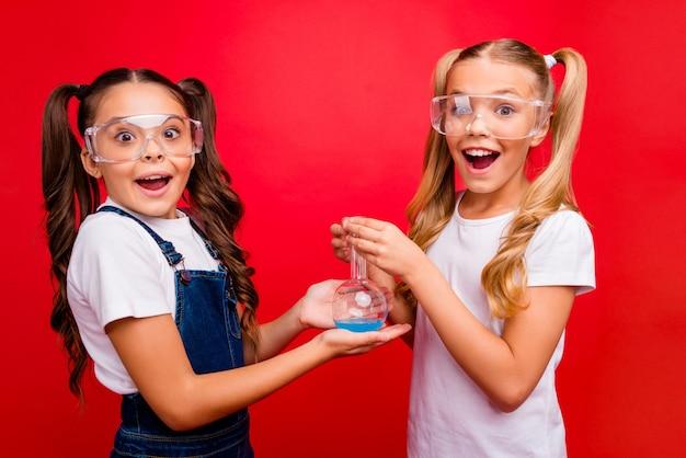 Фото двух забавных маленьких женщин прилежные школьники проводят химический эксперимент, захватывающие результаты, держат трубку, носить джинсы, общую белую футболку, изолированную красным ярким цветом
