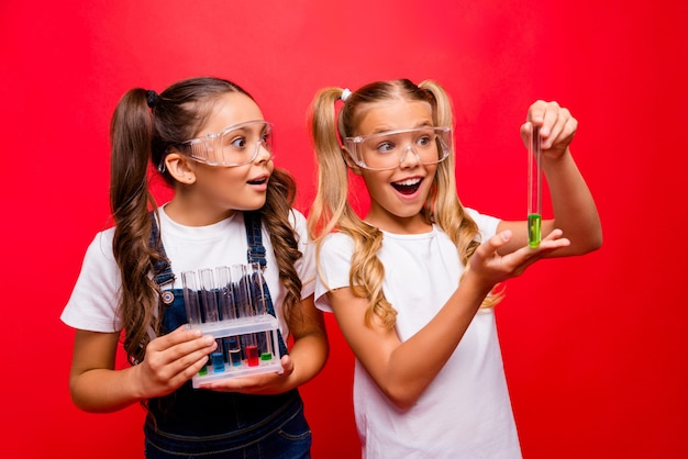 Фотография двух забавных маленьких дам, прилежных школьников, которые проводят химический эксперимент, захватывающие результаты, держат характеристики безопасности одежды в трубках, общая футболка, изолированные на красном фоне