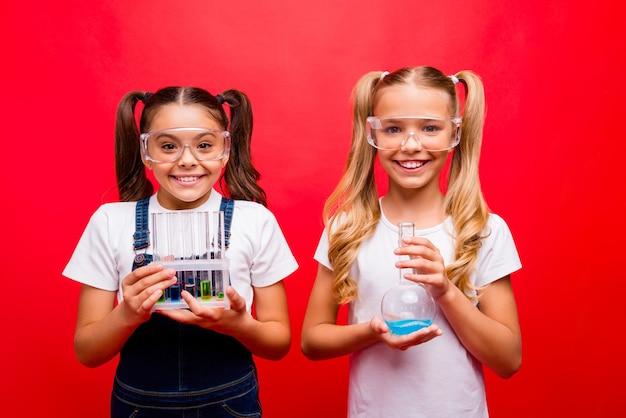 두 명의 재미있는 작은 숙녀 학교 아이들의 사진은 교사에게 튜브에서 결과를 보여주는 화학 실험을 안전 사양 전체 티셔츠 격리 된 붉은 색 배경을 착용합니다