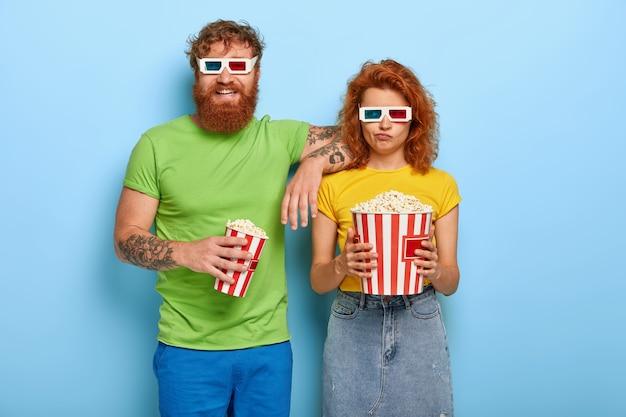 恋に落ちた2人のガールフレンドとボーイフレンドの写真は、映画館を訪れるのに適切な時間を選択します