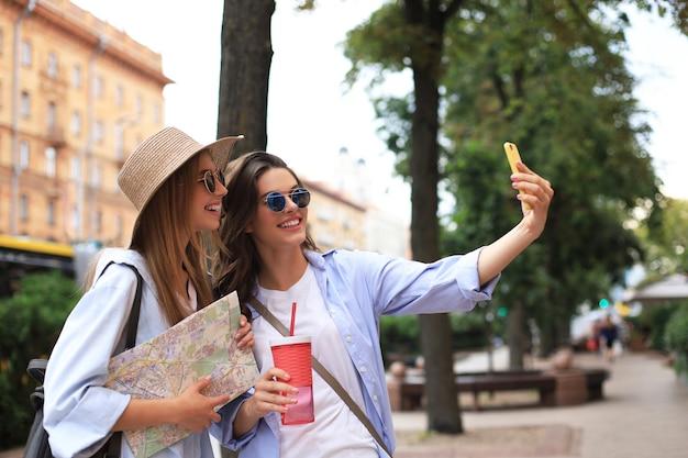 屋外観光を楽しんでいる2人の女の子の写真。地図で街を探索し、自分撮りをする美しい女性観光客。