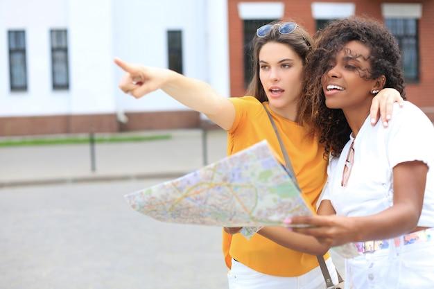 屋外観光を楽しんでいる2人の女の子の写真。地図で街を探索する美しい女性観光客。