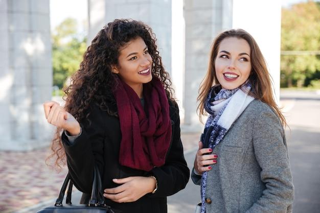 スカーフコミュニケーションを身に着けている2人のゴージャスな若い女性の写真。バッグを持っています。脇を見てください。
