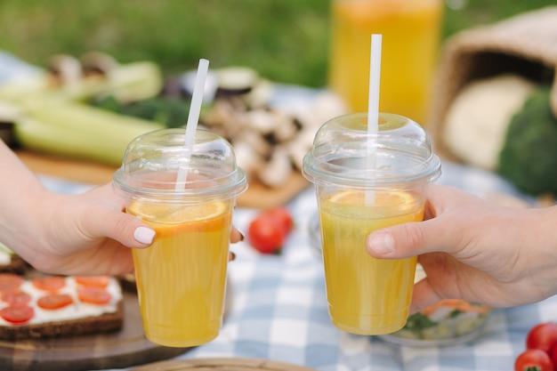屋外でビーガンピクニックの前でオレンジレモネードを持っている両手の写真