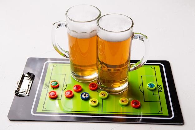 泡立つビールの2つのマグカップ、白いテーブルの上のテーブルサッカーの写真