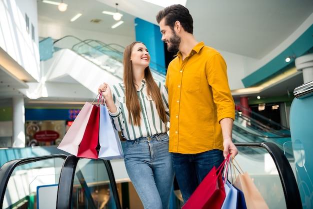 二人の写真は魅力的な女性を応援しますハンサムな男のカップルは自由な時間を楽しんでいますエスカレーターショッピングセンターを下に移動する多くのバッグを運ぶハグルック目は屋内でカジュアルなジーンズシャツの服を着ます