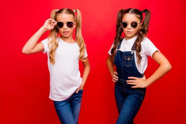 두 예쁜 작은 숙 녀 긴 꼬리의 사진 카메라를보고 자신감을 입고 멋진 태양 사양 청바지 전체 흰색 티셔츠 고립 된 빨간색 밝은 색 배경